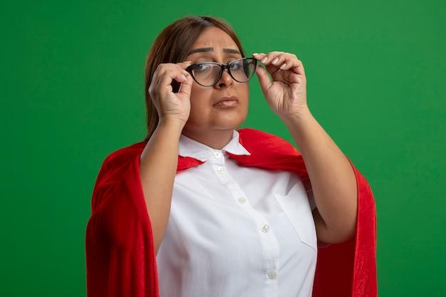 Strikte superheldvrouw van middelbare leeftijd die een bril draagt en grijpt die op groen wordt geïsoleerd