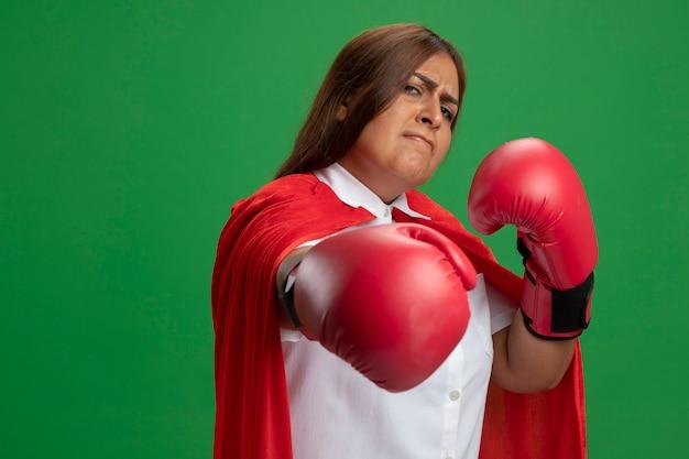 Strikte superheldwijfje dat van middelbare leeftijd bokshandschoenen draagt die hand uitsteken die op groen wordt geïsoleerd