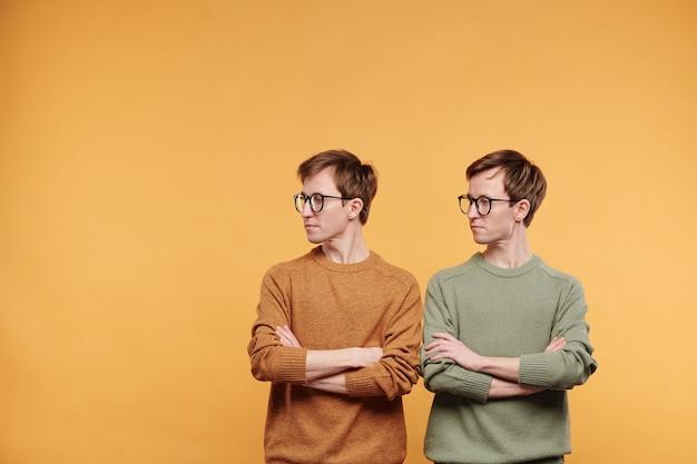 Strikte tweeling in glazen en lichte truien die met gekruiste armen staan en opzij kijken, oranje achtergrond