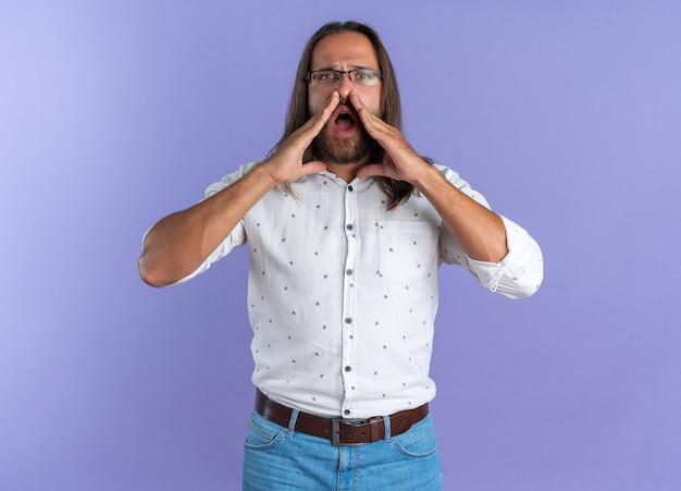 Strikte volwassen knappe man met een bril die naar de camera kijkt en zijn handen in de buurt van de mond houdt en schreeuwt geïsoleerd op een paarse muur