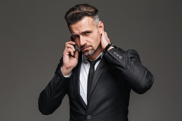 Strikte volwassen man in zwart pak op zoek op camera tijdens een mobiel gesprek, geïsoleerde over donkergrijs
