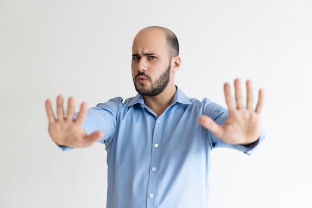 Strikte zakenman die handstop teken toont