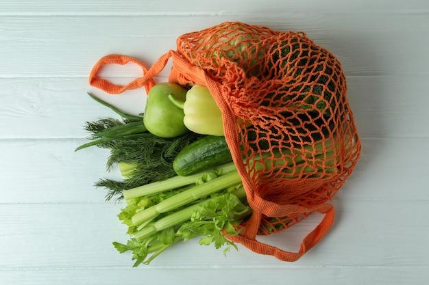 String tas met groene groenten op witte houten achtergrond