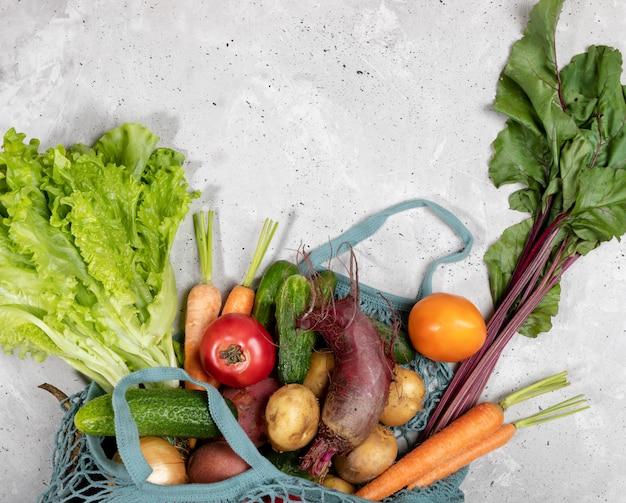 String tas met verse boerderij groenten op grijze betonnen achtergrond.