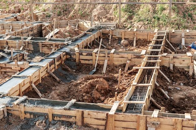 Strip funderingen met bekisting tijdens de bouw van een huis. betrouwbare fundering van gewapend beton. bouwplaats.