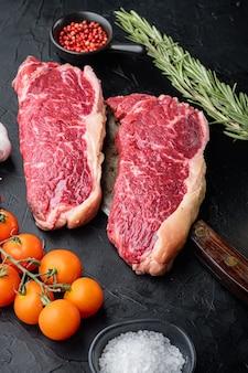 Strip steak, gemarmerd rundvlees rauw vlees, op zwarte achtergrond