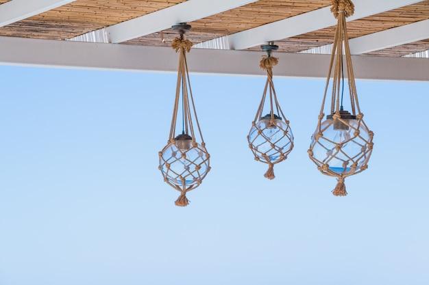 Stro bedekt het dak van een terras aan zee met hangende lantaarn.