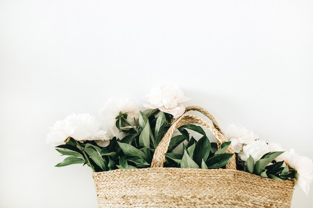 Stro handtas met witte pioenroos bloemen op wit oppervlak