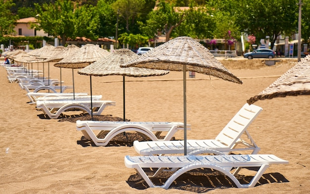 Stro parasols met ligstoelen op een strand
