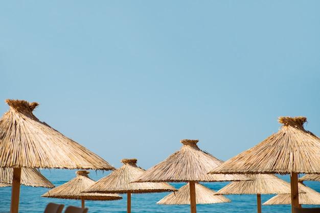 Stro strand parasols op een blauwe lucht en zee achtergrond met een kopie ruimte