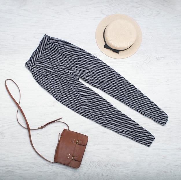 Strohoed, blauwe broek, handtas