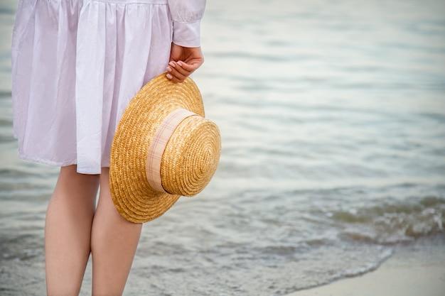Strohoed in vrouwelijke hand aan kust bij zonsondergang. onherkenbare vrouw in witte strandjurk met rust bij zonsondergang op zee strand. vrouw geniet van vakantie en vrijheid op het strand bij zonsondergang. ruimte kopiëren.