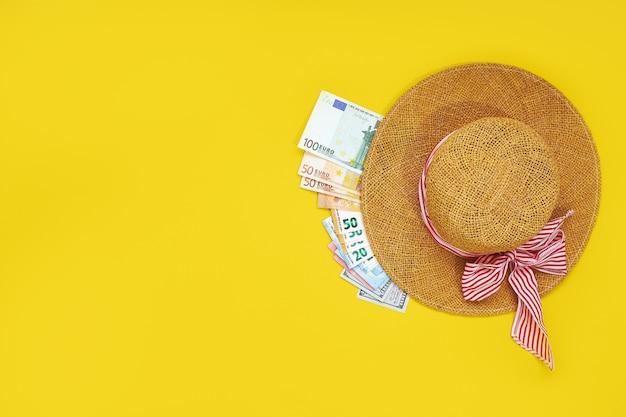 Strohoed met euro rekeningen op een gele achtergrond worden geïsoleerd die