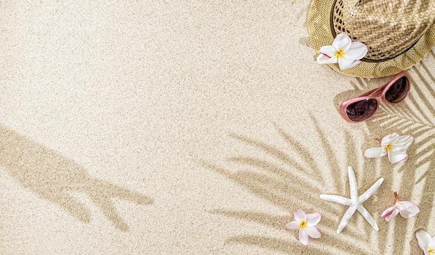 Strohoed met frangipanibloemen, zeeschelpen en zonnebril op wit zand met palmboom en handschaduw. zomerconcept met kopieerruimte
