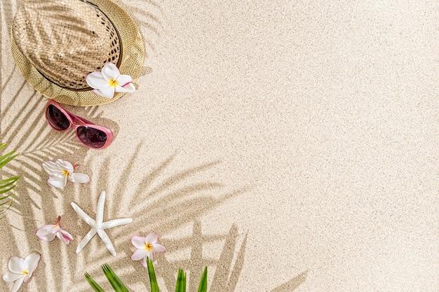 Strohoed met frangipanibloemen, zeeschelpen en zonnebril op wit zand <met palmboomschaduw.