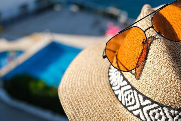 . strohoed met zonnebril houten terras van vakantievilla of hotel met stoeltafel met uitzicht op zee en zwembad.
