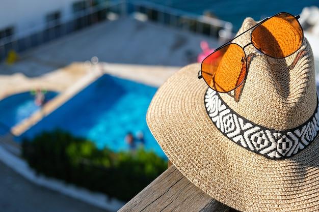 Strohoed met zonnebril houten terras van vakantievilla of hotel met stoeltafel met uitzicht op zee en zwembad.