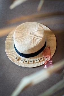Strohoed, roze zonnebril en houten letters. woord zomer. zomer achtergrond. vakantie, weekend