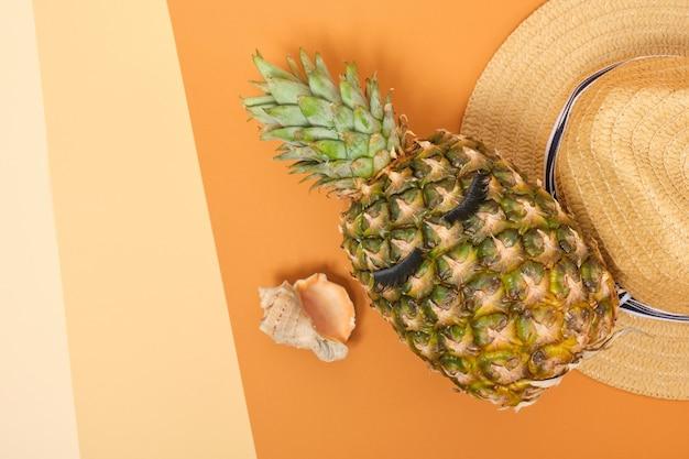 Strohoed, schelp en verse ananas met wimpers op oranje en lichtoranje achtergrond, bovenaanzicht