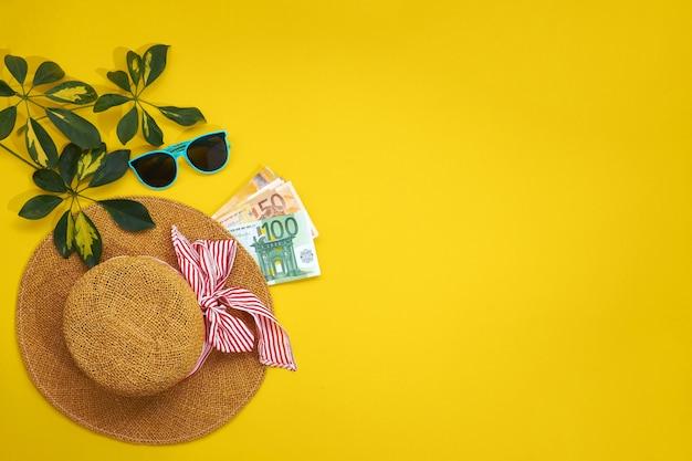 Strohoed, zonnebril en bladeren sheflers geïsoleerd op een gele achtergrond