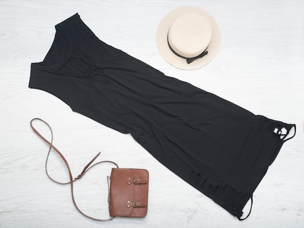 Strohoed, zwarte jurk, handtas