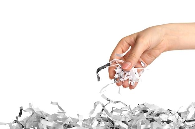 Stroken van vernietigd papier uit shredder in vrouwelijke hand geïsoleerd op wit