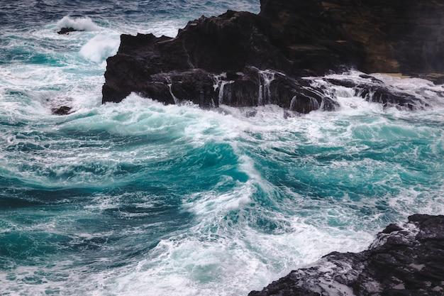 Stromyweer met grote golven bij rotsachtige kustlijn van het eiland van oahu, hawaï