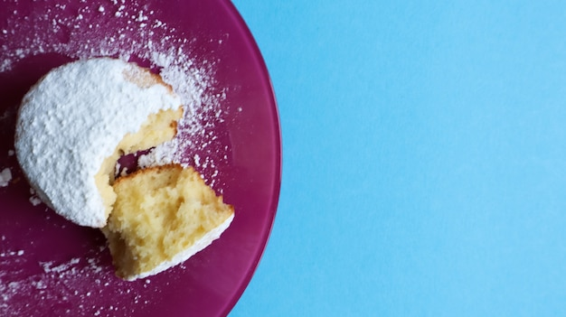 Strooi een kwark met poedersuiker op een roze bord, op een blauwe achtergrond, bovenaanzicht. dessert, een kleine cupcake. voedselconcept. witgebakken koekjes met een luchtige structuur. ruimte kopiëren.