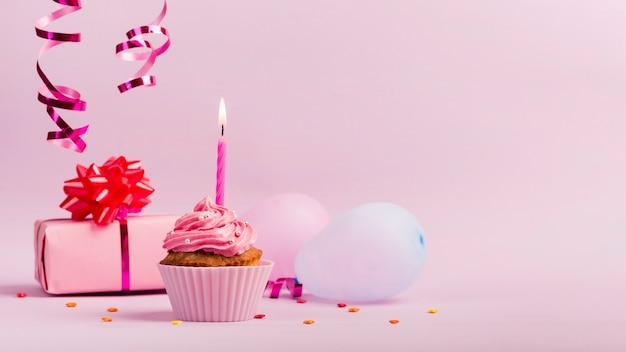 Strooi over de geschenkdoos; ballonnen en muffins met brandende kaars op roze achtergrond