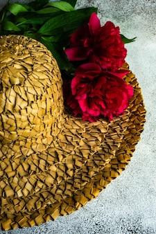 Strooien har versierd met felrode pioenroos bloemen op betonnen tafel