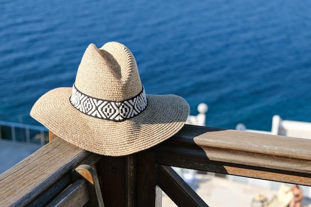 Strooien hoed op houten terras uitzicht op zee en het zwembad