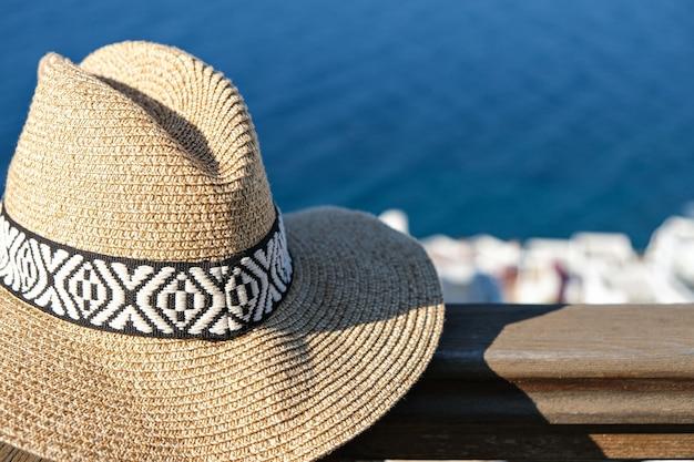 Strooien hoed op houten terras van vakantievilla met uitzicht op zee en het zwembad