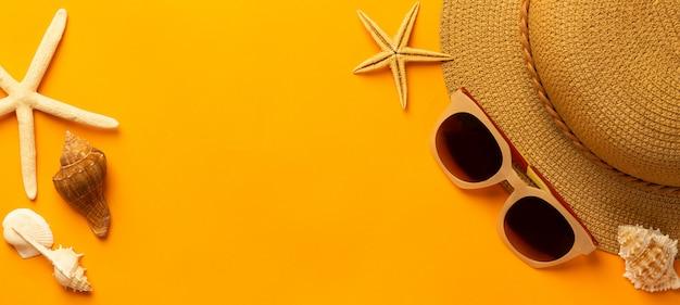 Strooien hoed, zonnebril en schelpen op levendige oranje tafel