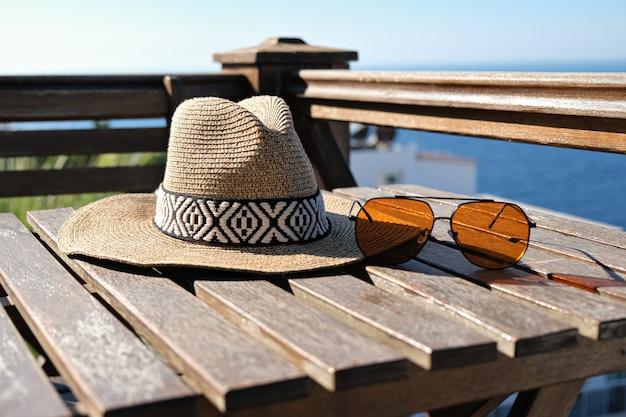 Strooien hoed zonnebril op houten terras uitzicht op zee en het zwembad