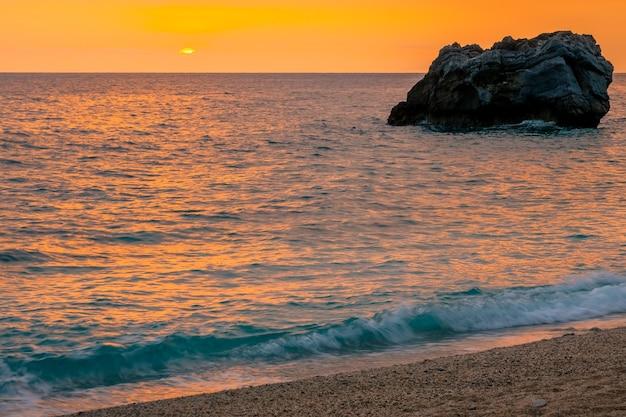 Strook zandstrand aan de griekse kust van de middellandse zee. veelkleurige zonsopgang boven kalm water