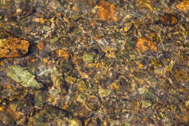 Stroom met helder water met stenen aan de onderkant