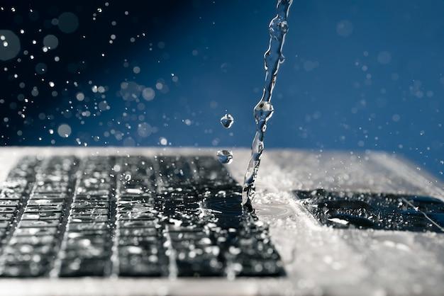 Stroom van water giet op het toetsenbord van de laptop.