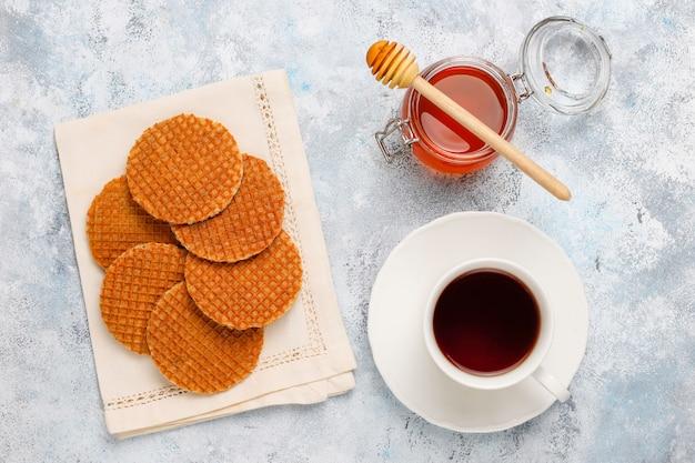 Stroopwafels, caramel dutch wafels met thee of koffie en honing op beton