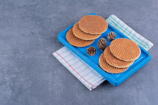Stroopwafels geïsoleerd in een blauwe houten plaat op een steen. foto van hoge kwaliteit