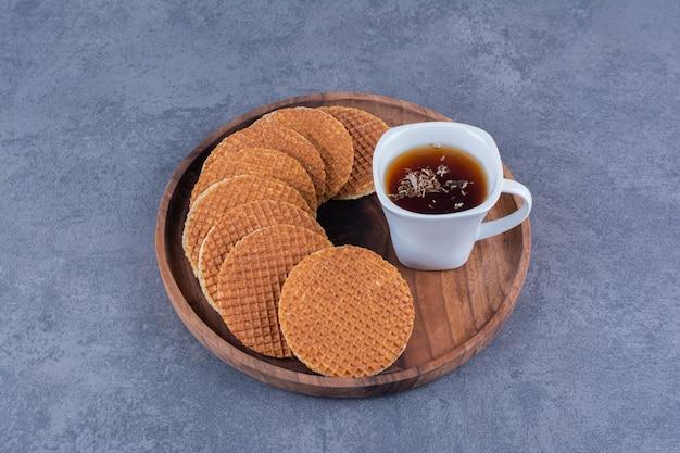 Stroopwafels met een witte kop thee geïsoleerd in een houten plaat op een steen.