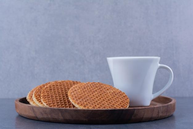 Stroopwafels met een witte kop thee geïsoleerd in een houten plaat op een stenen ondergrond