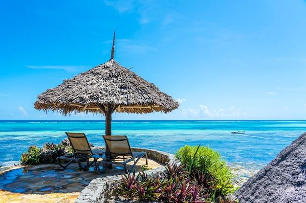 Stroparaplu en twee houten ligbedden op een tropisch strand in de buurt van de zee in zonnige dag op het eiland zanzibar, tanzania, oost-afrika