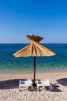 Stroparaplu op het prachtige strand van oprna op het eiland krk, in kroatië