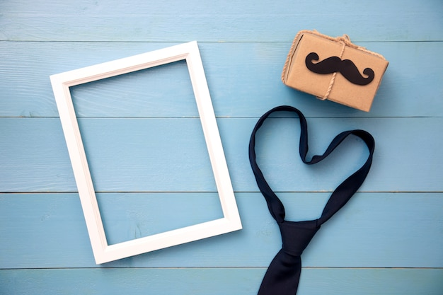 Stropdas, geschenkdoos, papieren snor, fotolijst op houten achtergrond met kopie ruimte. gelukkige vaderdag.
