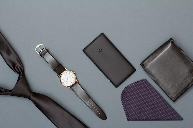 Stropdas, horloge met een zwarte leren band, mobiele telefoon, zakdoek en lederen tas op grijze achtergrond. accessoires voor heren. bovenaanzicht met kopieerruimte