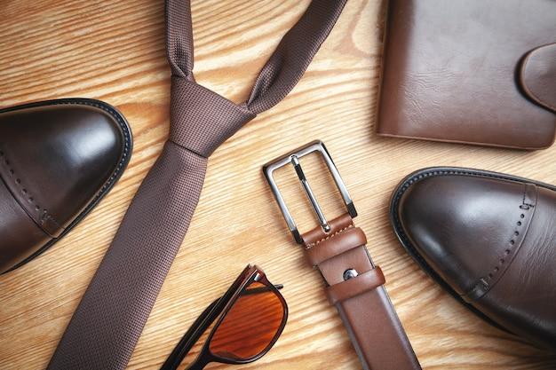 Stropdas, riem, portemonnee, schoenen, zonnebril op de houten achtergrond.