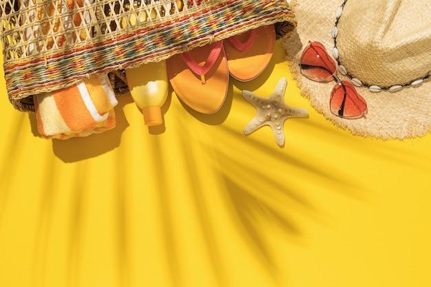 Strozak met accessoires voor strandvakantie op gele achtergrond en palmbladschaduw met kopie ruimte
