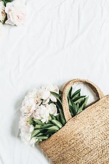 Strozak met witte pioenroos bloemen op wit oppervlak