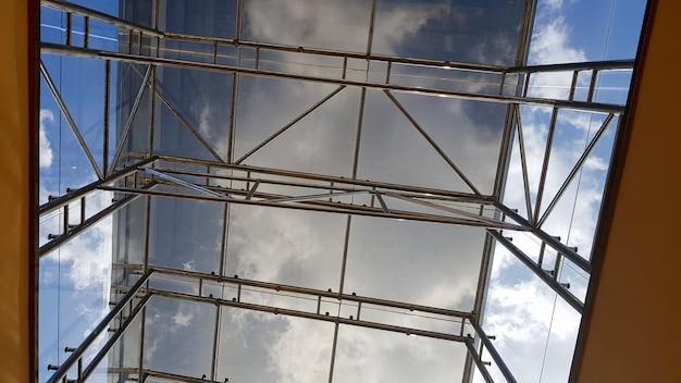 Structurele beglazing van de gevel. abstracte achtergrond met glazen plafondelementen in een modern gebouw. zicht op de blauwe lucht door een glazen raam, gescheiden door roosterelementen.