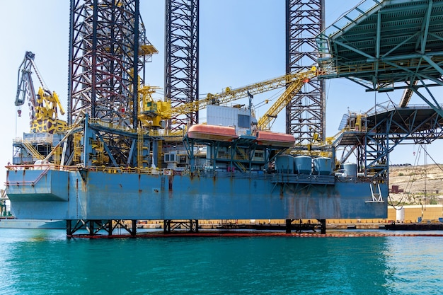 Structuren met apparatuur voor het boren van oliebronnen bevinden zich in de zee in de buurt van een kust van malta op de achtergrond van de blauwe lucht.